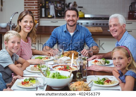 Portrait of smiling multi generation family sitting at dining table