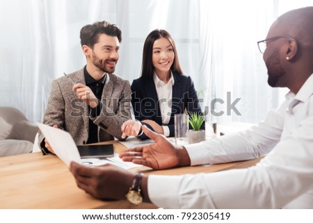 Portrait of  smiling multinational businessmen and businesswoman sitting at the table and discussing new project while working together in office isolated