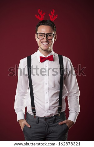 Portrait of smiling nerdy man with christmas horns - stock photo
