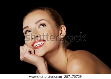 Portrait of smiling nude woman on dark background. - stock photo