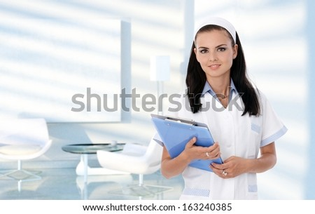 Portrait of smiling nurse in clinic waiting room, healthcare, medical. - stock photo