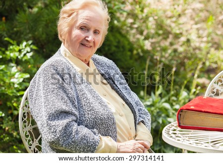 Portrait of smiling old grandmother. Photo on nature background.  - stock photo