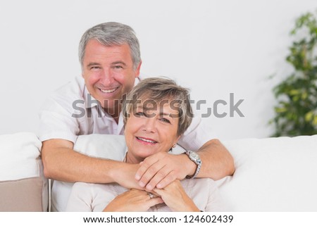 Portrait of smiling old lovers in sitting room - stock photo