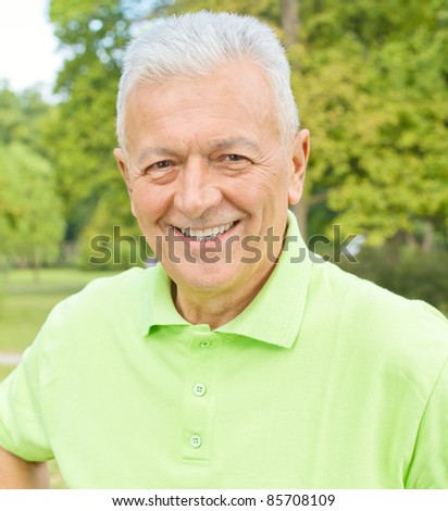 Portrait of smiling old man in the park. - stock photo