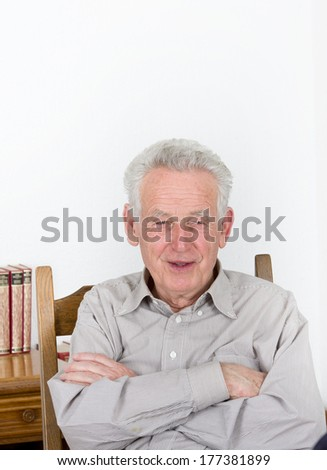 Portrait of smiling old man with crossed arms - stock photo