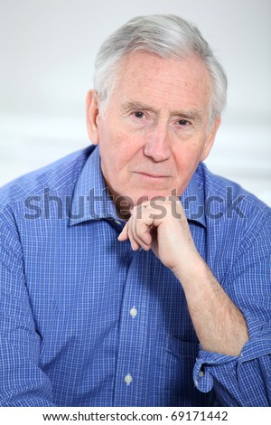 Portrait of smiling old man with hand on chin - stock photo
