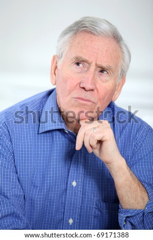 Portrait of smiling old man with thoughtful look - stock photo