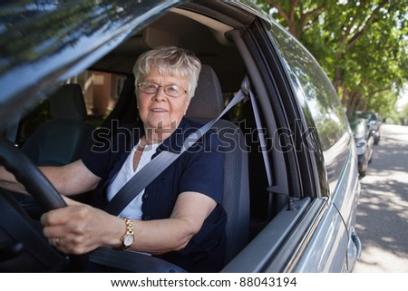 Portrait of smiling old woman driving car - stock photo