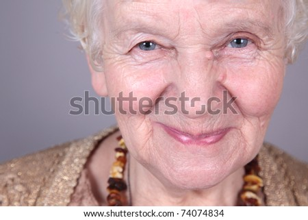 Portrait of smiling old woman. isolated against grey background - stock photo