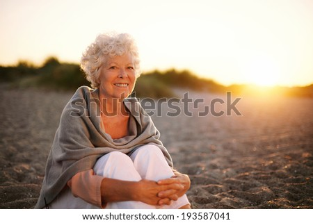 Portrait of smiling old woman sitting on the beach. Senior caucasian female relaxing outdoors - stock photo