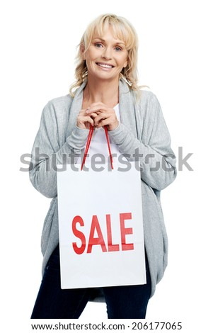 Portrait of smiling older woman holding shopping bag with SALE sign on it - stock photo