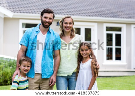 Portrait of smiling parents with children standing outside house in yard