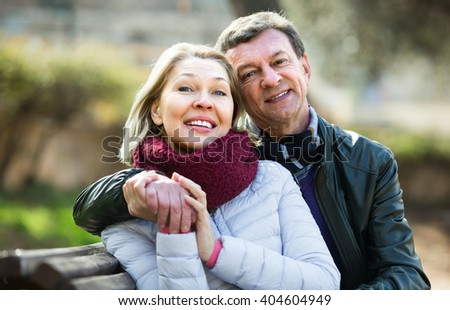 Portrait of smiling pensioners couple cuddling in park at spring day - stock photo