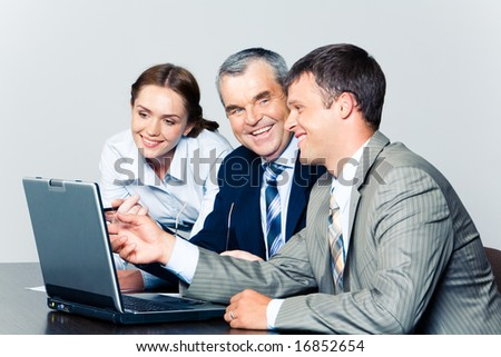 Portrait of smiling people discussing a computer work together at workplace