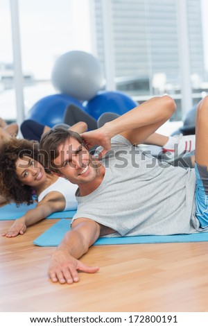 Portrait of smiling people doing pilate exercises in the fitness studio - stock photo