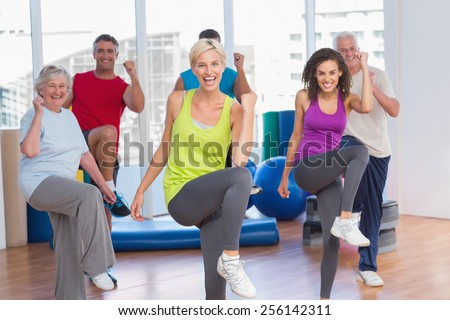 Portrait of smiling people doing power fitness exercise at fitness studio - stock photo