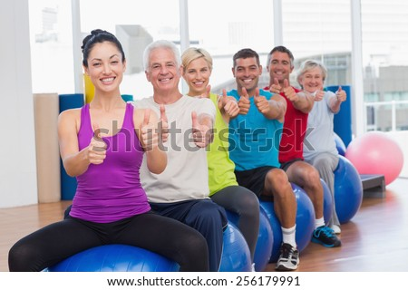 Portrait of smiling people sitting on exercising balls gesturing thumbs up in gym - stock photo