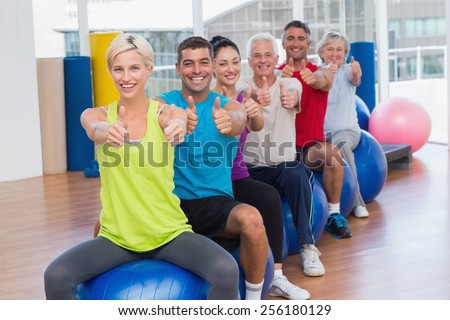 Portrait of smiling people sitting on exercising balls gesturing thumbs up in health club - stock photo