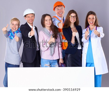 Portrait of smiling people with various occupations holding blank billboard showing ok - stock photo