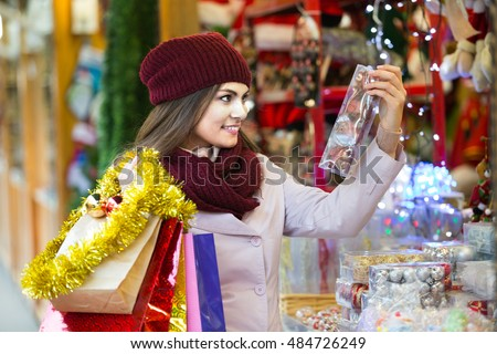Portrait of smiling person near counter with Christmas gifts