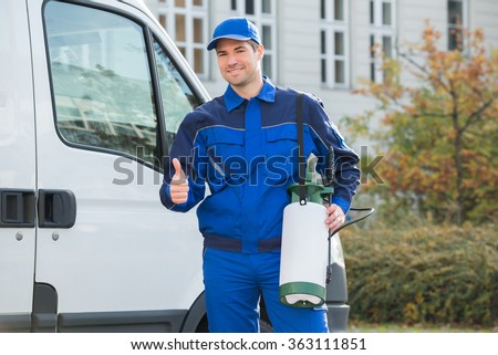 Portrait of smiling pest control worker showing thumbsup while standing by truck - stock photo