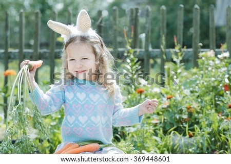Portrait of smiling preschooler blonde girl with Easter bunny DIY ears and fresh carrots - stock photo