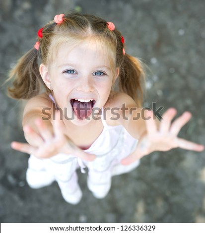 Portrait of smiling pretty little girl with hands up - stock photo