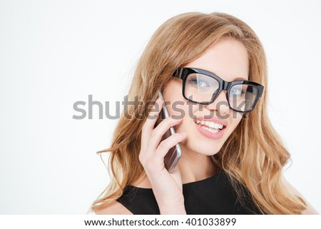 Portrait of smiling pretty young business woman in glasses talking on cell phone over white background