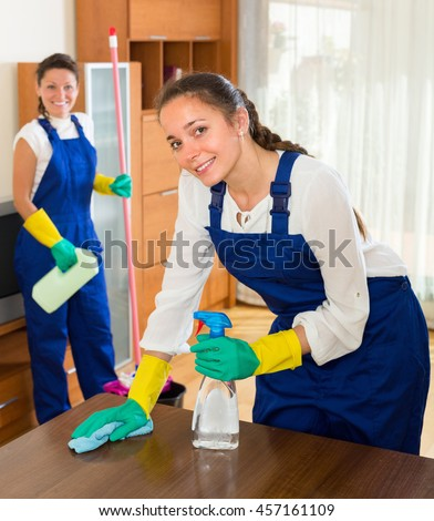 Portrait of smiling professional cleaners washing apartment with rag and mop