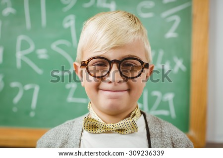 Portrait of smiling pupil dressed up as teacher in a classroom in school - stock photo