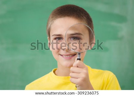 Portrait of smiling pupil looking through magnifier in a classroom in school - stock photo
