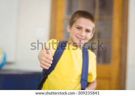 Portrait of smiling pupil with schoolbag doing thumbs up in a classroom in school - stock photo