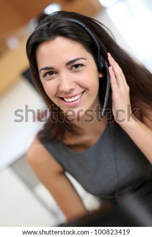 Portrait of smiling receptionist with headphones - stock photo
