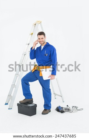 Portrait of smiling repairman with toolbox and ladder using cellphone against white background - stock photo
