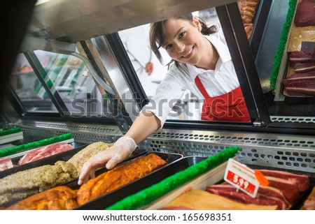 Portrait of smiling saleswoman picking meat displayed in cabinet at butcher's shop - stock photo