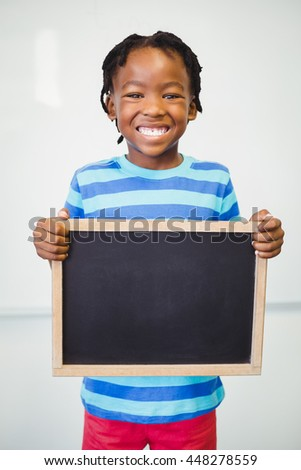 Portrait of smiling school boy holding slate in classroom at school - stock photo