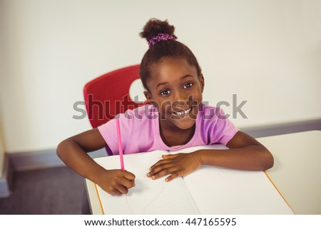 Portrait of smiling school girl doing homework in classroom at school