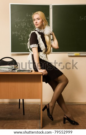 Portrait of smiling school girl in a classroom - stock photo