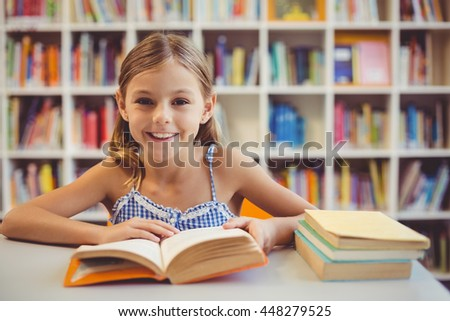 Portrait of smiling school girl reading a book in library at school - stock photo