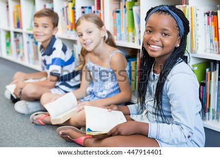 Portrait of smiling school kids sitting on floor and reading book in library - stock photo