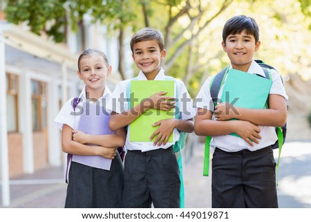 Portrait of smiling school kids standing in campus with books at school - stock photo