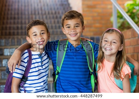 Portrait of smiling school kids standing with arm around at school - stock photo