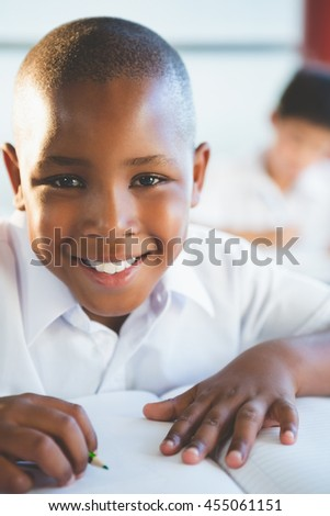 Portrait of smiling schoolboy doing homework in classroom at school - stock photo