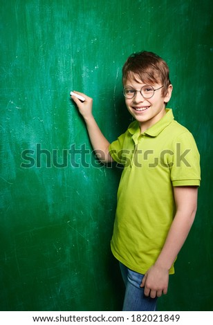 Portrait of smiling schoolboy in eyeglasses looking at camera by the blackboard