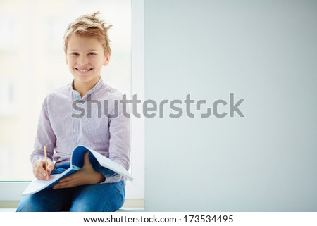 Portrait of smiling schoolboy making notes in exercise-book - stock photo