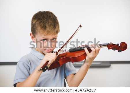 Portrait of smiling schoolboy playing violin in classroom at school - stock photo