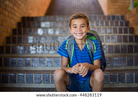 Portrait of smiling schoolboy sitting on staircase at school - stock photo