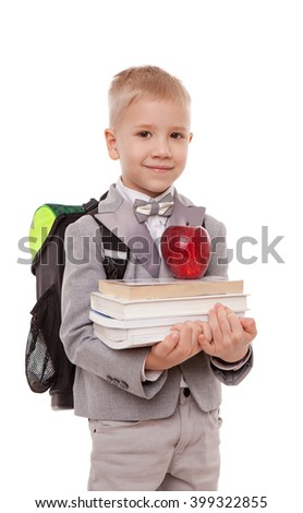 Portrait of smiling schoolboy with backpack holding book and apple isolated on white background - stock photo