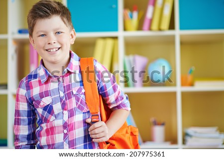 Portrait of smiling schoolboy with backpack looking at camera - stock photo