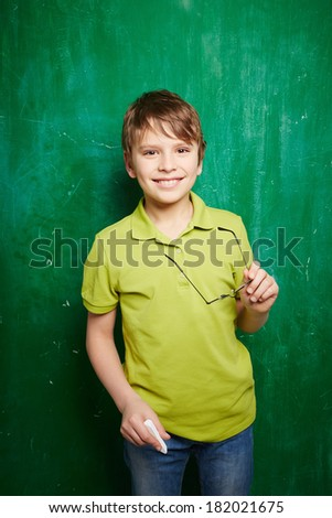 Portrait of smiling schoolboy with chalk and eyeglasses looking at camera by the blackboard - stock photo